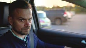 Mannautofahren, nach einer Parkmöglichkeit suchend stock video footage