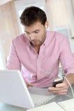 MannBüroangestellter auf Laptop zu Hause Stockbild