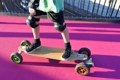 Mannbeinfahrten auf ein elektrisches Skateboard Stockfotos