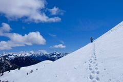 Mannbergsteiger auf steilem Schneeberghang Stockbilder