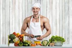 Mannbodybuilder, der auf Küche kocht stockbild
