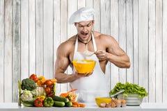 Mannbodybuilder, der auf Küche kocht lizenzfreie stockfotos