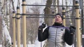 Mannbodybuilder, der untersetzte Übung auf Sportplatz im Winterpark tut stock video footage