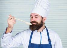 Mannchef-Geschmacksuppe vom hölzernen Löffel Küche kulinarisch vitamin Nährendes biologisches Lebensmittel Glücklicher bärtiger M stockfotografie