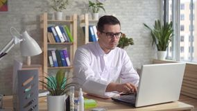 Manndoktor, der an Laptop am Schreibtisch arbeitet stock video