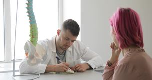 Manndoktor und geduldige Frau mit den rosa Haaren besprechen Diagnose unter Verwendung des Dornmodells stock video