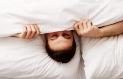 Mannederlag i säng under ark Royaltyfri Foto