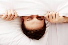 Mannederlag i säng under ark Royaltyfria Bilder