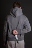Mannederlagkniv bak hans baksida över grå färger Arkivfoton