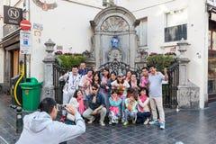 Manneken Pis雕象的中国游人在布鲁塞尔 图库摄影