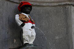 Manneken Pis in Brussels. Belgium (Little man Pee) - a landmark small bronze sculpture depicting a naked little boy urinating into a fountain's Royalty Free Stock Photos