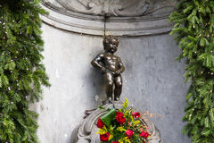 Manneken Pis Bruxelles. Manneken Pis Of Bruxelles with red flowers royalty free stock photo