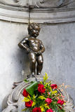 Manneken Pis Bruxelles. Manneken Pis Of Bruxelles with red flowers stock image