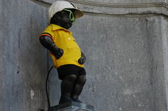 Manneken Pis dressed in one of the costium. Manneken Pis little man pee a landmark small bronze sculpture in Brussels, Belgium, depicting a naked little boy Stock Photo