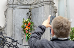 Manneken Pis with flowers prepared for a ceremony of award of costume Stock Image