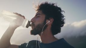 Mannelijk atleten drinkwater van fles stock footage