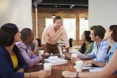 Mannelijk Chef- Addressing Office Workers op Vergadering Stock Foto