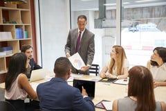 Mannelijk chef- holdingsdocument op een bedrijfsbestuurskamervergadering stock foto's
