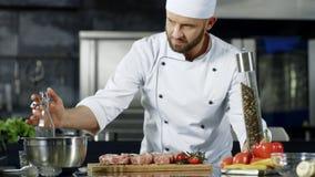 Mannelijk chef-kok kokend vlees bij professionele keuken Portret van chef-kok kokend lapje vlees stock video