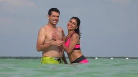 Mannelijk en Vrouwelijk Paar die Badpakken in Oceaan dragen stock footage
