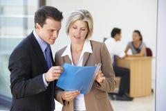 Mannelijk en Vrouwelijk Uitvoerend het Bespreken Rapport met Bureauvergadering op Achtergrond royalty-vrije stock foto