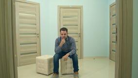 Mannelijk geduldig wachten voor artsen` s benoeming die zijn hoofd neigen en de camera onderzoeken Stock Foto