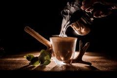 Mannelijk hand gietend water van waterkruik in de koffiekop Royalty-vrije Stock Foto's
