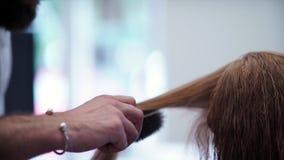 Mannelijk hand het borstelen woman's haar De professionele kapper gebruikte een borstel stock video