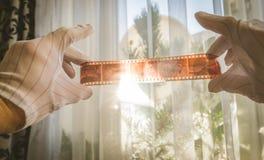 Mannelijk handenbeeld die de Oude uitstekende 35mm film Negatieve Kijker met behulp van om kaders op de zonsondergangachtergrond  stock foto