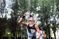 Mannelijk heet het weer gietend water van de atletenagent op hoofd stock fotografie