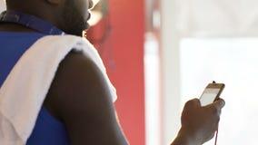 Mannelijk het zoeken contact van vriend op mobiele telefoon plaatsende benoeming na gymnastiek stock videobeelden