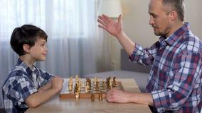 Mannelijk jong geitje winnend schaak met zijn vader, weinig zoon het schudden hand met papa, hobby stock footage