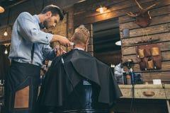 Mannelijk kappers scherp haar van klant in kapper royalty-vrije stock foto's