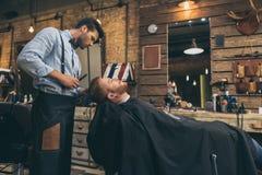 Mannelijk kappers scherp haar van klant in kapper royalty-vrije stock foto