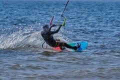 Mannelijk kiteboarder berijdt op een raad op een grote rivier Stock Afbeeldingen