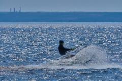 Mannelijk kiteboarder berijdt op een raad op een grote rivier Stock Fotografie