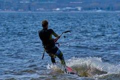 Mannelijk kiteboarder berijdt op een raad op een grote rivier Royalty-vrije Stock Fotografie