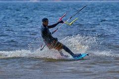 Mannelijk kiteboarder berijdt op een raad op een grote rivier Royalty-vrije Stock Foto's