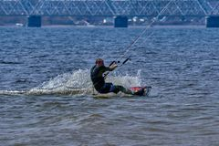 Mannelijk kiteboarder berijdt op een raad op een grote rivier Royalty-vrije Stock Afbeeldingen