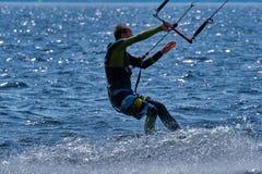 Mannelijk kiteboarder berijdt op een raad op een grote rivier Stock Foto