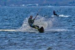 Mannelijk kiteboarder berijdt op een raad op een grote rivier Stock Afbeelding