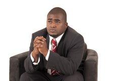 Mannelijk model in pak en rode gestreepte bandzitting als voorzitter Stock Fotografie