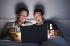 Mannelijk paar die in bed lachen, en op laptop drinken letten royalty-vrije stock afbeelding
