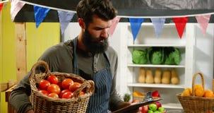 Mannelijk personeel die controlelijst bekijken en een mand van tomaten houden stock footage
