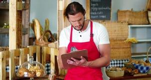 Mannelijk personeel die een controlelijst maken bij bakkerijteller stock video