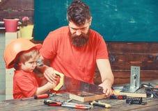 Mannelijk plichtenconcept Vader, ouder die met baard weinig zoon onderwijzen aan het zagen met scherpe handsaw, timmermansambacht stock fotografie