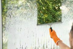 Mannelijk portier schoonmakend venster met squeege stock foto's