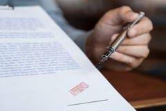 Mannelijk punt aan het ondertekenen van bedrijfsdocument voor het zetten van handtekening, vulpen en goedgekeurd gestempeld op ee royalty-vrije illustratie