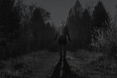 Mannelijk silhouet bij de donkere bosweg door de struiken in de nacht Mens die zich op de weg tegen de auto bevinden Stock Afbeeldingen