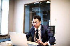 Mannelijk trots CEO holdingshandboek tijdens het werk aangaande draagbare netbook stock afbeeldingen